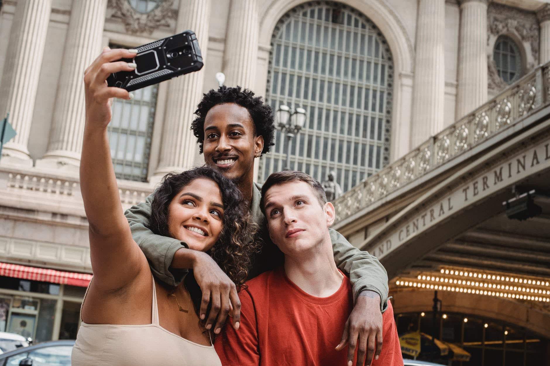 positive multiethnic friends taking selfie on modern smartphone near railway station building